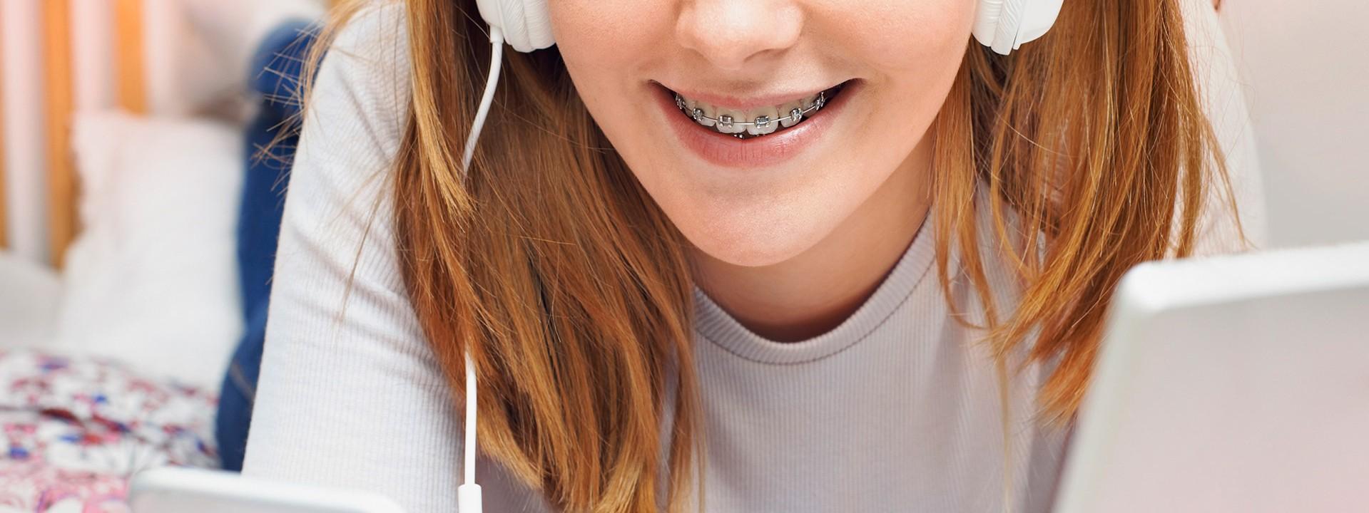 Der lächelnde Mund des jungen Mädchens gibt den Blick frei auf ihre Zahnspange.