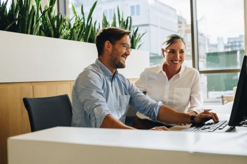 Ein Mann und eine Frau sitzen in einem Büro gemeinsam vor einem Computer. Der Mann tippt auf der Tastatur. Beide lächeln.