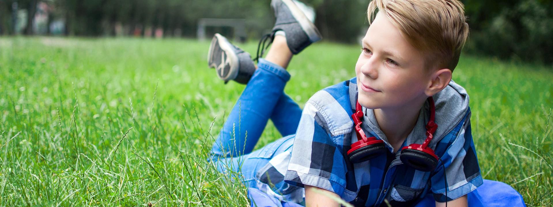 Junge liegt auf Wiese und schaut hoffnungsvoll