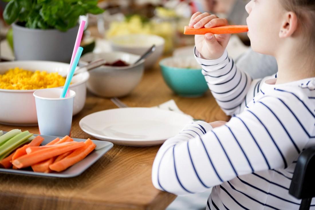 Mädchen mit Gemüse-Stick am Tisch