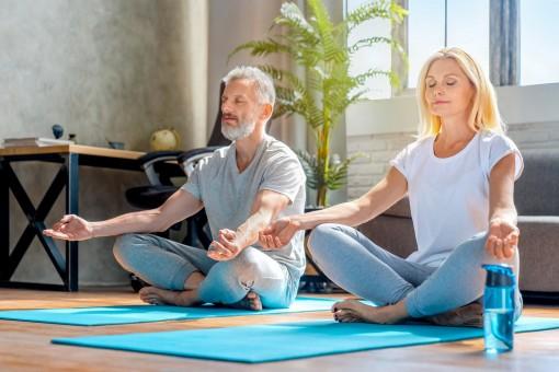 Ein etwa 60-jähriger Mann und eine 50-jährige Frau meditieren auf einer Yogamatte.