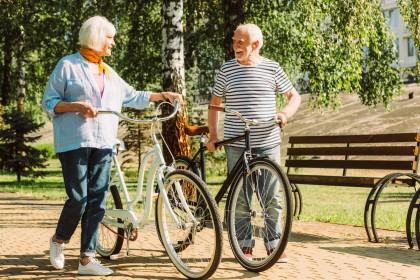 Ein Seniorenpaar steht mit ihren Fahrrädern auf einem Kiesweg in einem grünen Park.