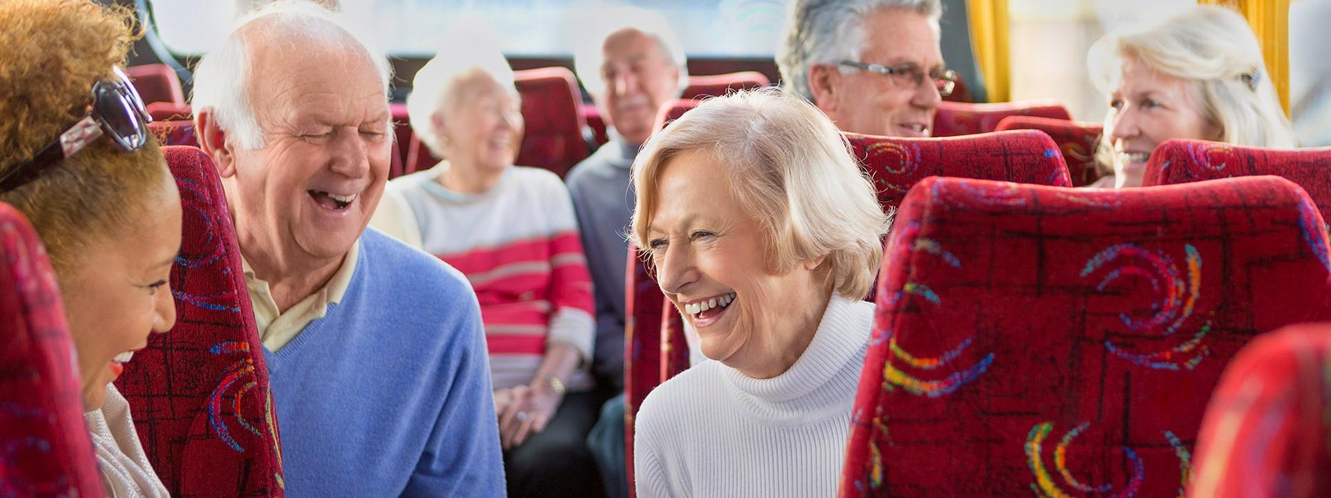 Senioren sitzen fröhlich in einem Reisebus.
