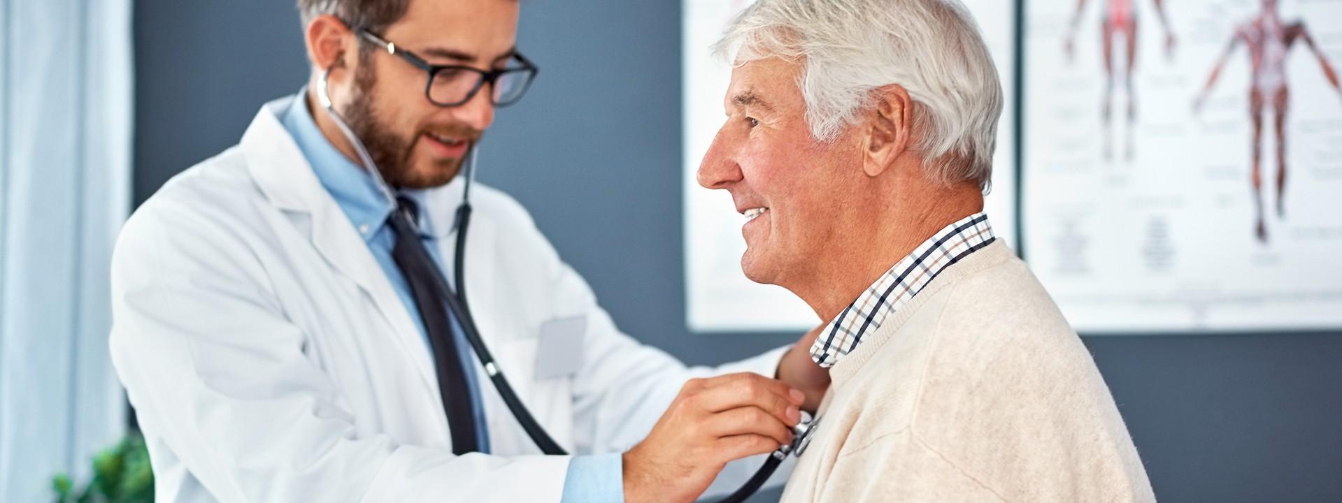Ein etwas 35 jähriger Mann untersucht mit einem Stethoskop einen Senioren. Beide befinden sich in einem Behandlungsraum und lächeln.