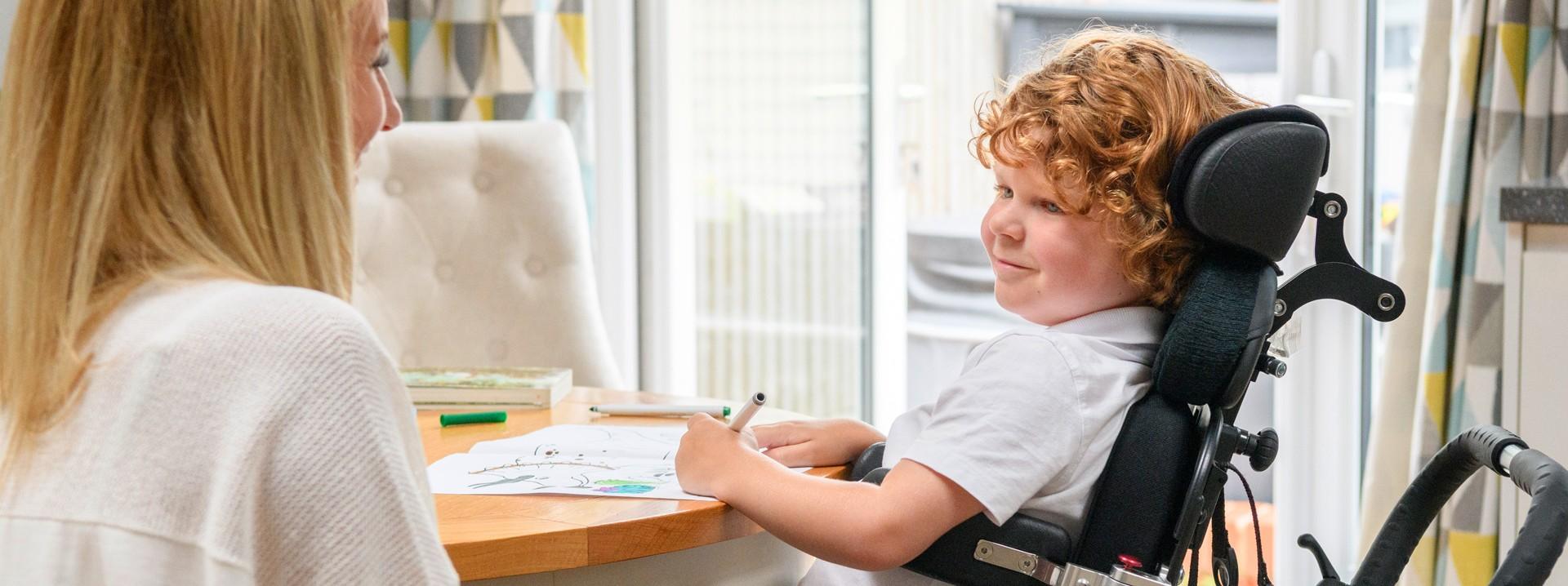 Ein etwa 10 jähriger Junge sitzt in einem Rollstuhl an einem Tisch und malt auf ein Blatt Papier. Ihm sitzt eine Frau mit einer Katze auf dem Schoß gegenüber.