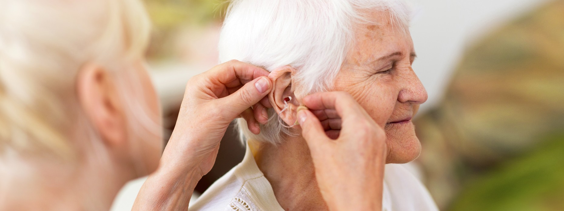 Einer Seniorin wird durch eine weibliche Person eine Hörhilfe in das Ohr eingesetzt.