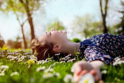 Lächelnde junge Frau liegt auf einer Wiese mit Gänseblümchen