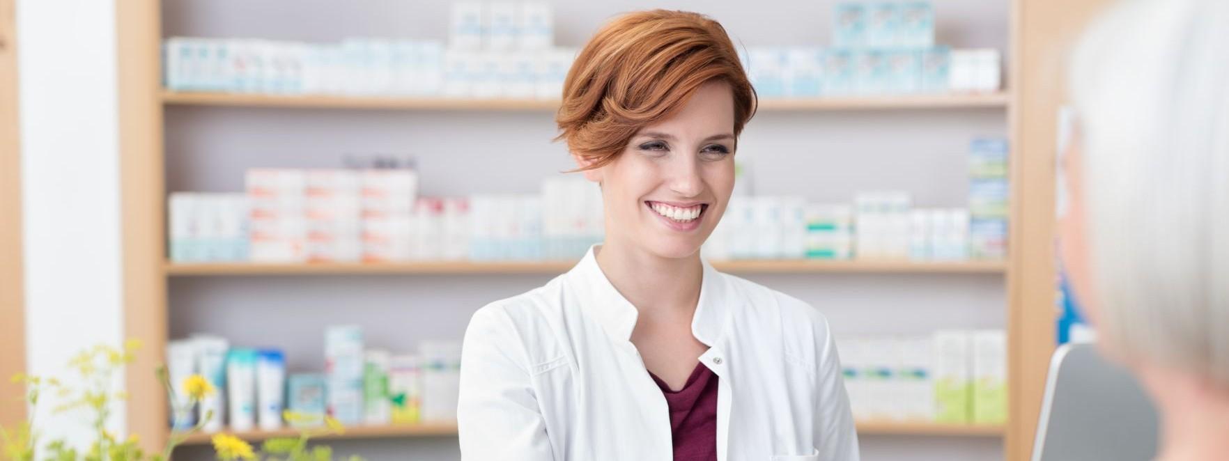 Eine Apothekerin gibt einer Frau ein Medikament über den Tresen aus. Im Hintergrund steht ein regal mit vielen weiteren Arzneimitteln.