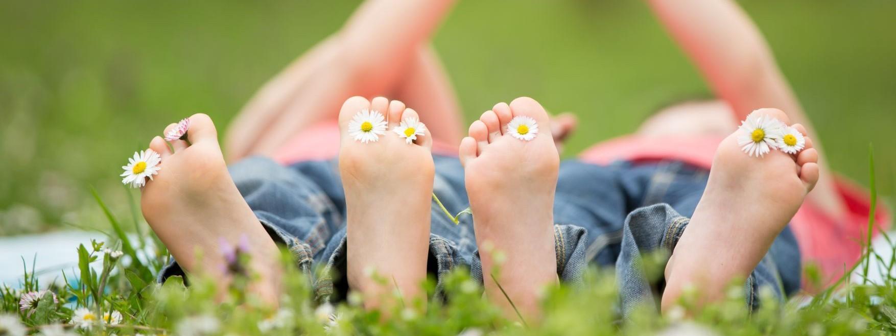 Zwei Kinder liegen auf einer Wiese. Sie sind barfuß, zwischen ihren Zehen stecken Gänseblümchen.