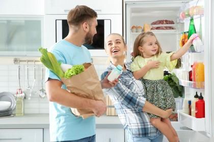 Eine junge Familie steht in der Küche und räumt Lebensmittel in den Kühlschrank ein. Die Frau lächelt dabei ihren Mann an und trägt ihr Kind auf dem Arm.