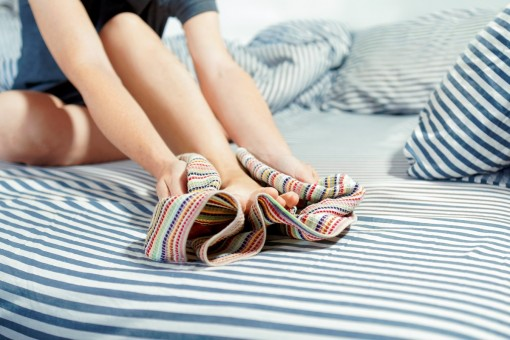 Eine Person sitzt auf dem Bett und trocknet sich sorgfältig mit einem Handtuch den linken Fuß ab.