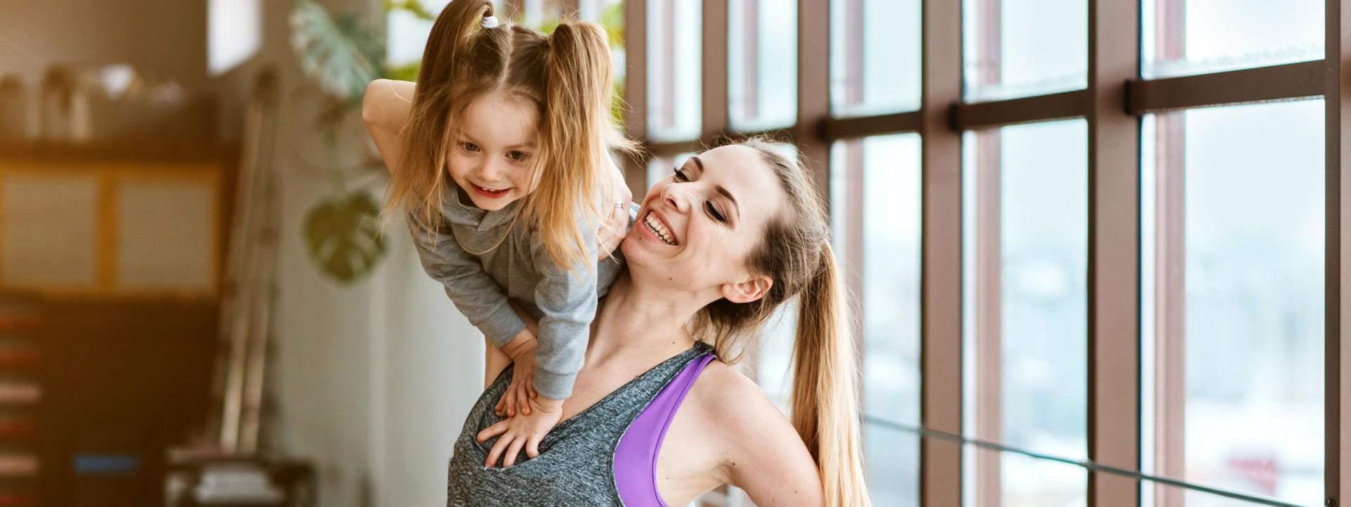 Eine etwa 35-jährige Mutter hat ihre circa 4- jährige Tochter auf der Schulter und beide lachen.