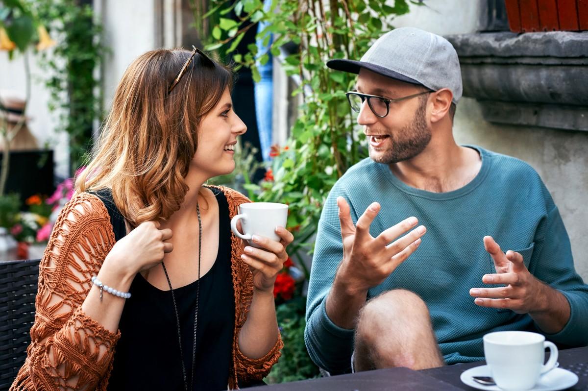 Ein Student und eine Studentin sitzen draußen vor einem Café und unterhalten sich