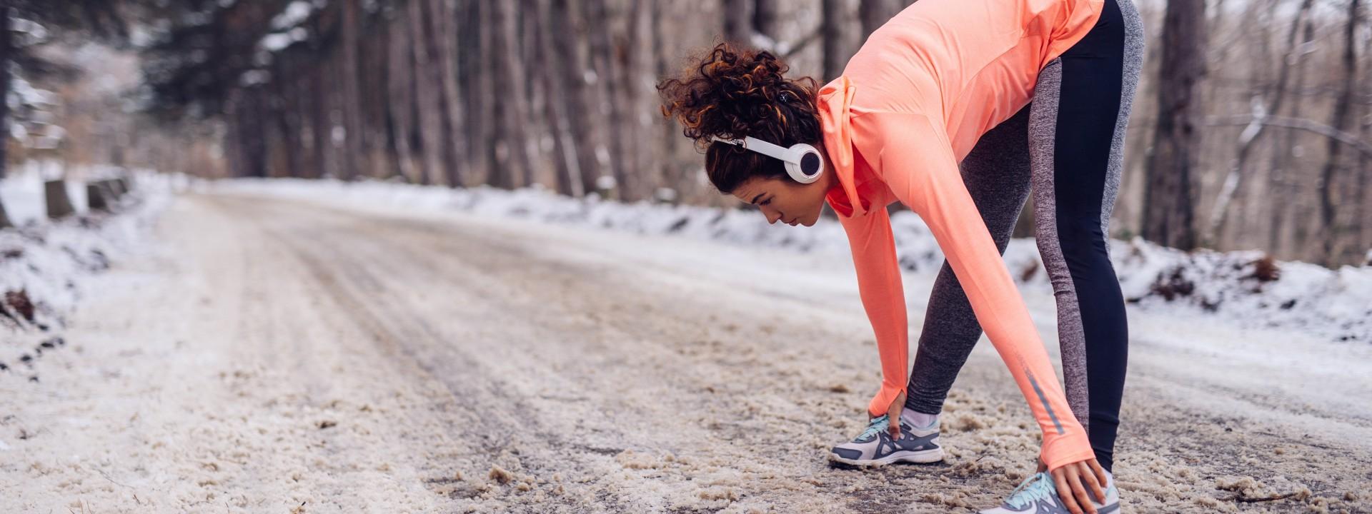 Eine etwas 30 jährige Frau steht an einer beschneiten Straße. Sie trägt Kopfhörer und dehnt ihre Beine.