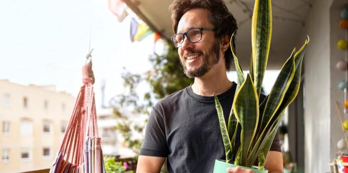 Mann steht mit Pflanze im Arm auf Balkon