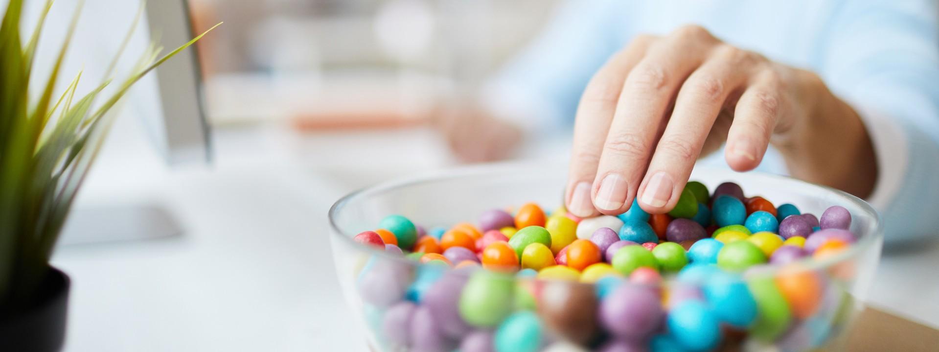 Frau greift in eine Schüssel mit Süßigkeiten