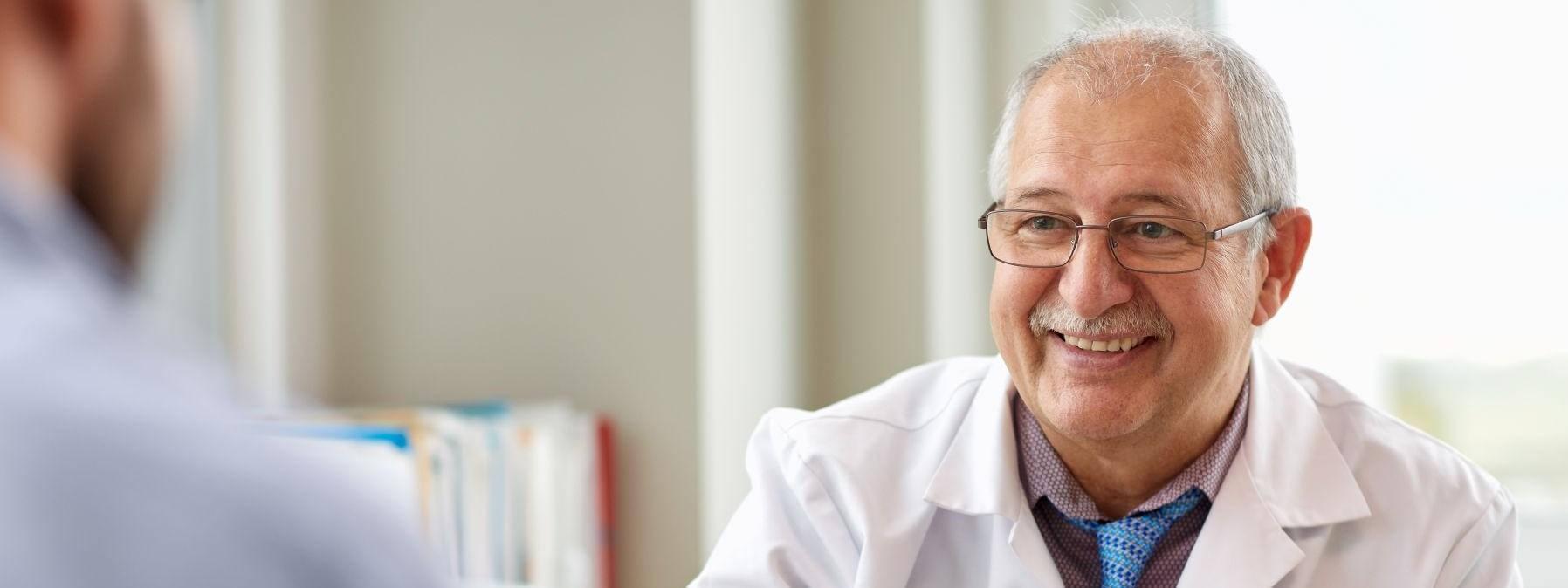 Ein etwa 60 jährige Arzt sitzt an seinem Beratungstisch und berät einen Patienten. Dabei lächelt er.