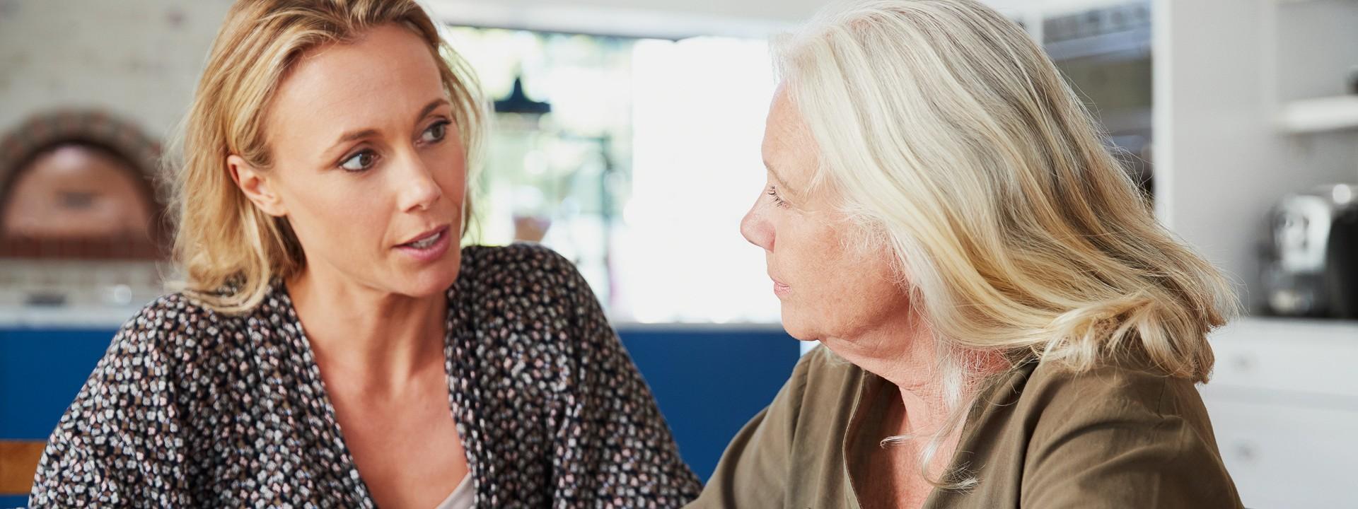Zwei Frauen sitzen in einer Wohnung am Tisch und unterhalten sich. Die rechte Frau hält in der rechten Hand einen Stift und macht Notizen.