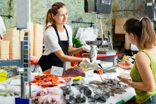 Eine Frau kauft an einem Fischstand frischen Fisch bei einer Verkäuferin.