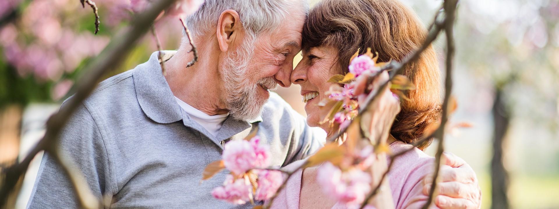Ein Seniorpaar umarmt sich im Park unter einem blühenden Kirschbaum.