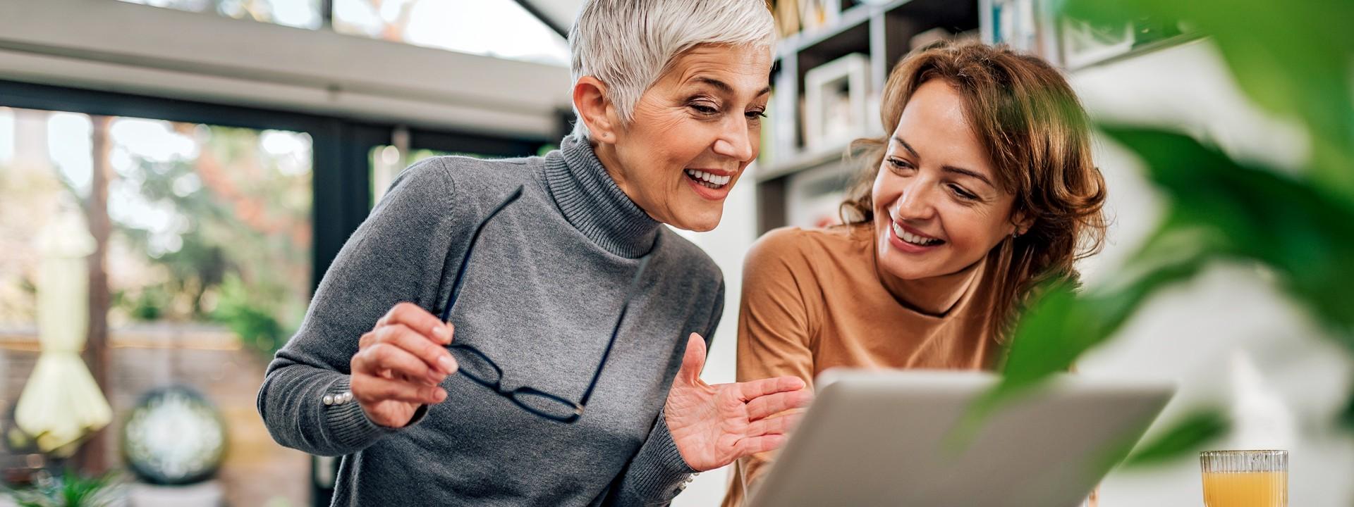 Eine Seniorin mit einer Brille in der Hand und eine etwa 40 jährige Frau sitzen an einem Tisch. Vor ihnen steht ein Laptop und beide lächeln.