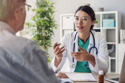 Eine Ärztin sitzt an einem Tisch und berät einen Patienten. Auf dem Tisch stehen ein Laptop und eine Packung Tabletten.