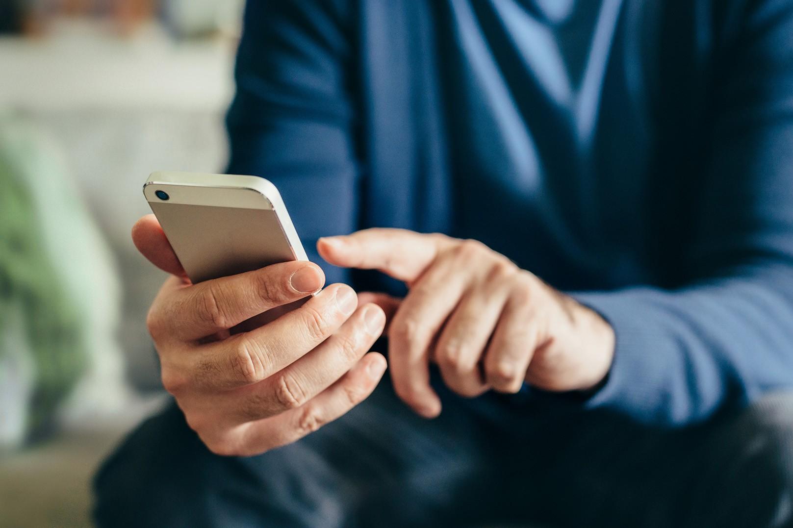 Männerhände bedienen Smartphone