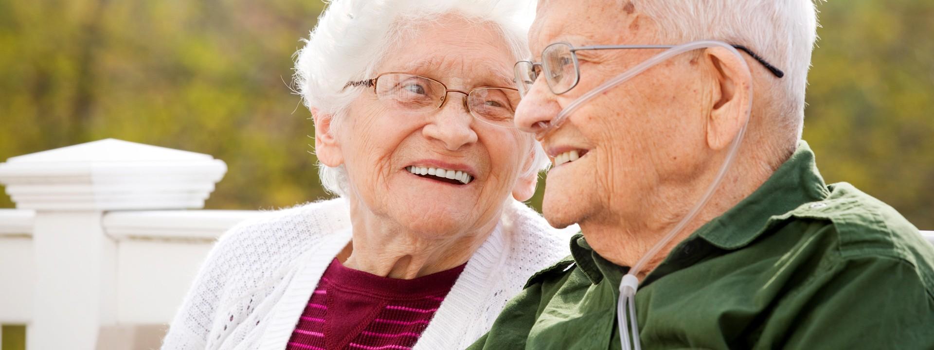 Ein Seniorenpaar sitzt auf einer weißen Bank und schauen sich lächeln an. Der Mann trägt ein Sauerstoffgerät.