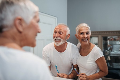 Ein etwa 60 jähriges Pärchen steht gemeinsam vor einem Spiegel im Bad und putzt sich die Zähne.