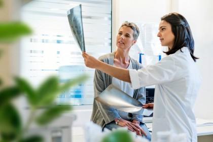 Eine Ärztin und eine Patientin schauen zusammen auf ein Röntgenbild