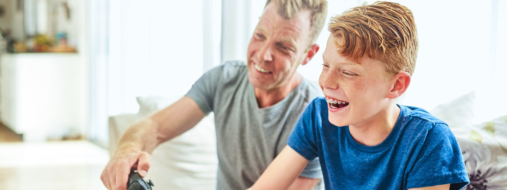 Ein Junge mit blauen Tshirt und Zahnspange sitzt mit einem erwachsenen Mann auf dem Sofa und spielt auf der Spielkonsole.