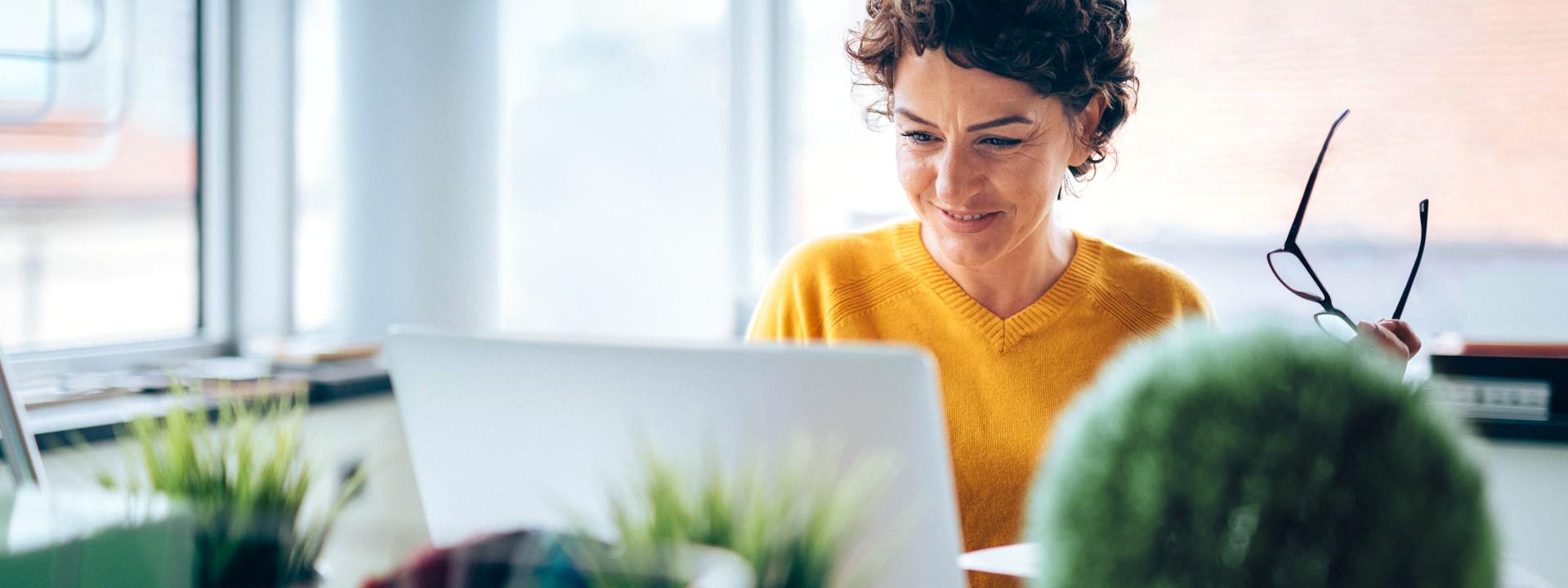 Eine brünette Frau hat eine Brille in der linken Hand, sitzt an einem Schreibtisch und schaut auf Ihren Laptop.