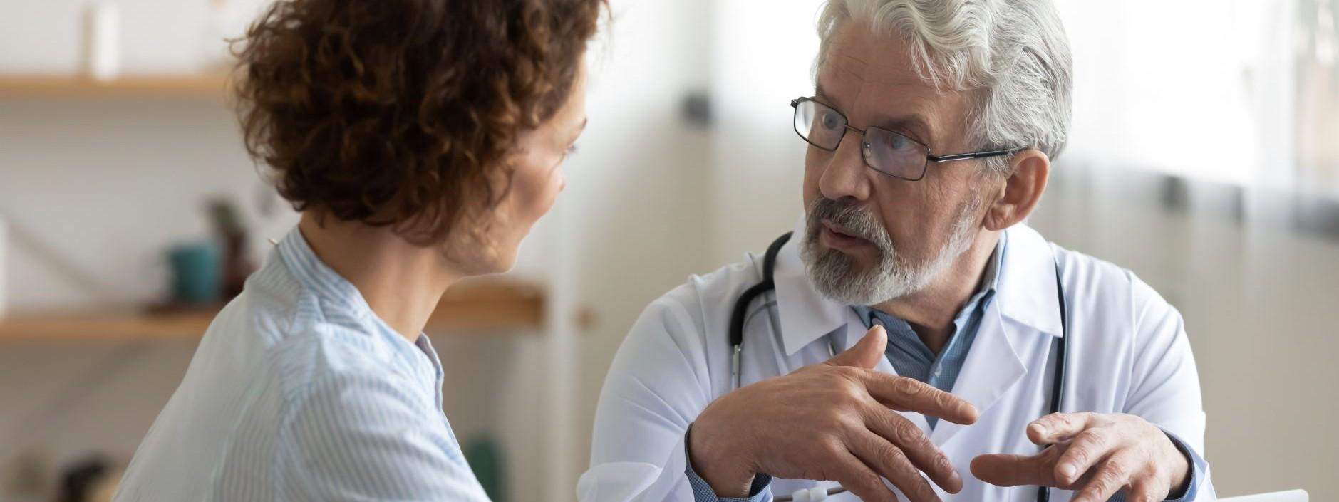 Eine etwa 45 jährige Frau sitzt bei einem Arzt im Behandlungszimmer. Der Arzt berät sie. Vor ihnen steht auf dem Tisch ein Laptop.