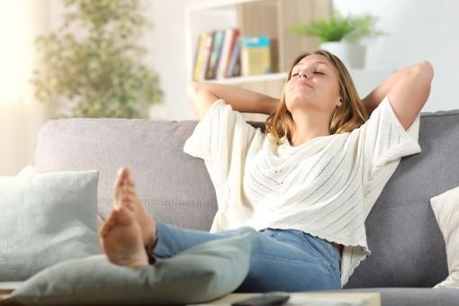 Eine etwa 30 jährige Frau sitzt auf einem Sofa und hat die Beine nach oben gelegt. Sie lehnt nach hinten, hat ihre Arme hinter dem Kopf verschränkt und die Augen geschlossen.