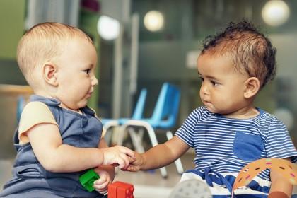 Zwei Kleinkinder schauen sich an und reichen sich die Hand.