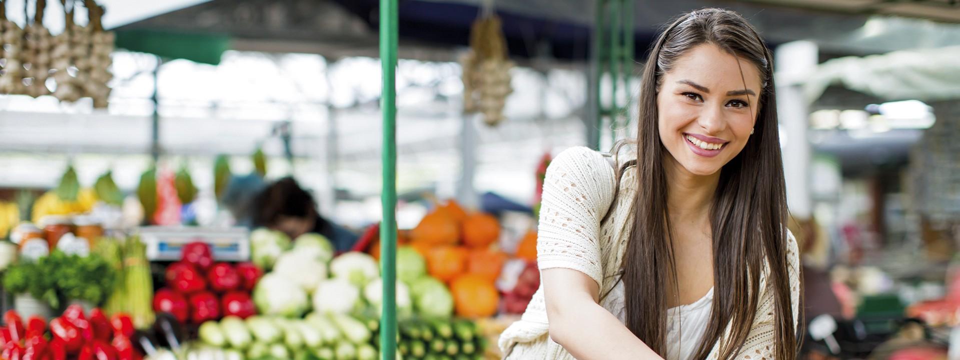 Eine junge brünette Frau kauft auf einem Markt Gemüse ein und lächelt.