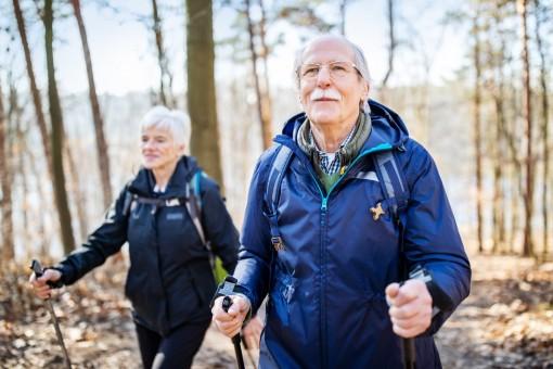 Ein Seniorenpaar läuft mit Nordic-Walking-Stöckern durch den Wald.