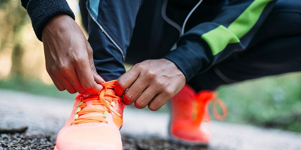 Mann bindet seine Laufschuhe zu