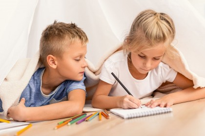 Ein etwa 6 jähriges Mädchen liegt unter einer Decke und malt konzentiert auf einen Noitzblock. Ein etwa 6 jähriger Junge liegt daneben und schaut ihr interessiert zu.