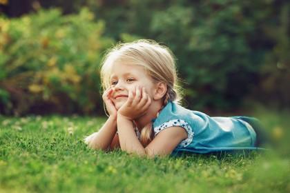 Kleines blondes Mädchen liegt auf grüner Wiese.