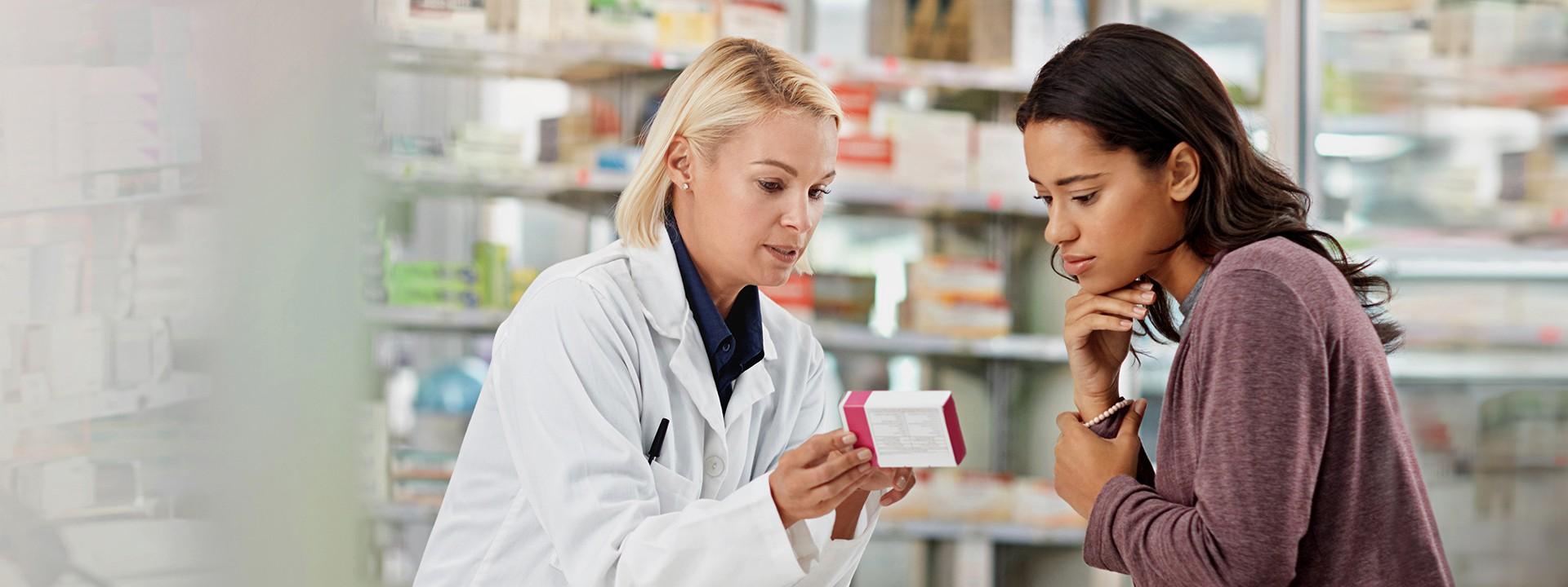 Eine Frau wird in der Apotheke von der Apothekerin zu einem Arzneimittel beraten.