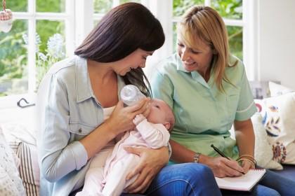 Zwei Frauen füttern ein Baby mit Flasche.