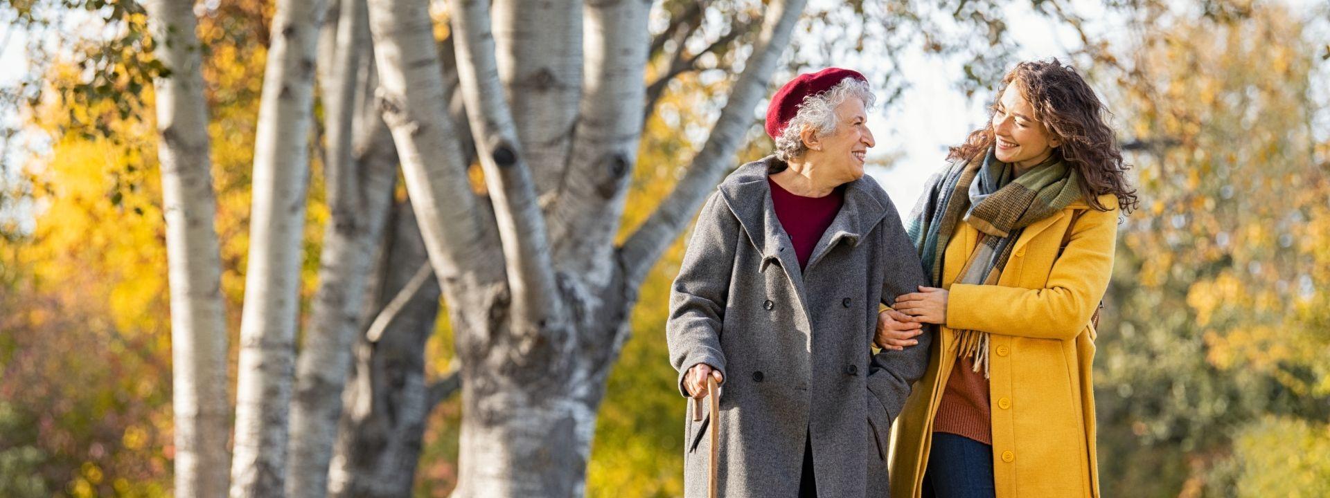 Eine etwa 35 jährige Frau läuft mit einer Seniorin durch die Natur. dabei stützt sie die Seniorin. Beide schauen sich an und lächeln.