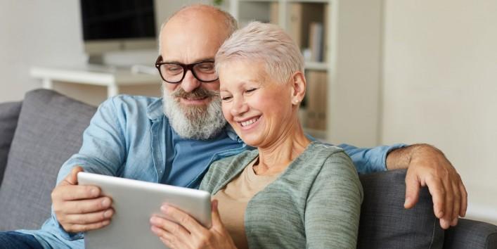 Ein älteres Pärchen sitzt auf einem Sofa und schaut gemeinsam auf ein Tablet. Beide lächeln.