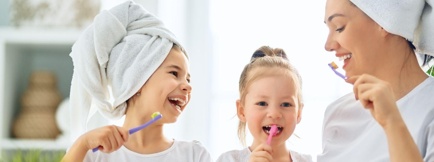 Eine Mutter putzt mit ihren zwei Töchtern die Zähne. Die Frau und das größere Mädchen haben Handtücher um ihren Kopf gewickelt.