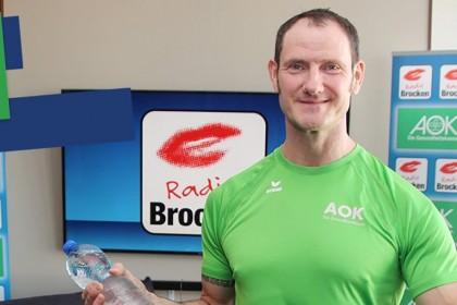 Ein etwas 40 jähriger sportliche Mann in einem grünen T-Shirt trägt Handtuch und eine Wasserflasche. Im Hintergrund sieht man das Radio Brocken-Studio.