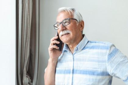 Ein Senior steht am Fenster und telefoniert mit einem Handy. Dabei schaut er aus dem Fenster.