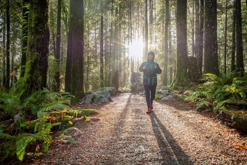 Frau mit Regenkleidung läuft duch Wald bei Sonnenuntergang.