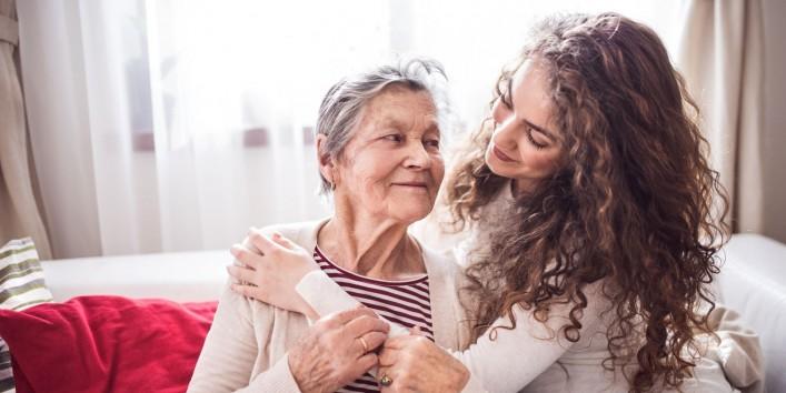 Eine etwa 30 jährige Frau umarmt eine Seniorin. Beide sitzen auf einem Sofa und lächeln sich gegenseitig an.