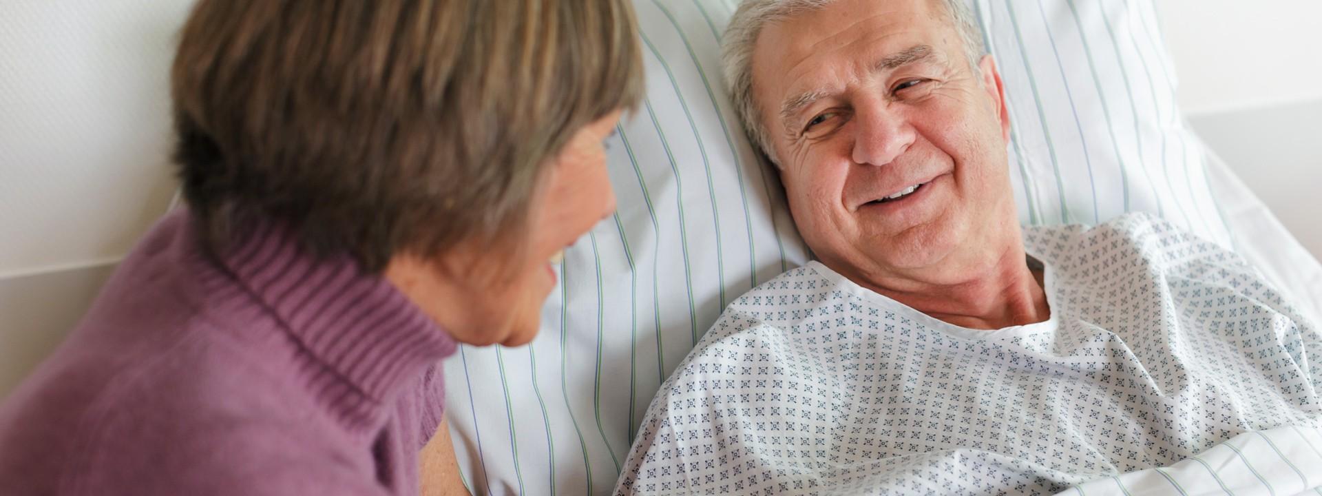 Ein älterer Mann liegt im Bett un spricht mit einer Frau.